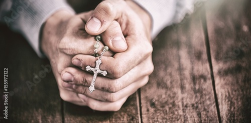Canvas Print Man praying with rosary