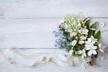 Bouquet Of Spring Flowers Lilies Of The Valley, Forget Me Not And Daisies On A Wooden Background