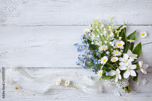 Poster Lelietje van dalen Bouquet of spring flowers lilies of the valley, forget me not and daisies on a wooden background