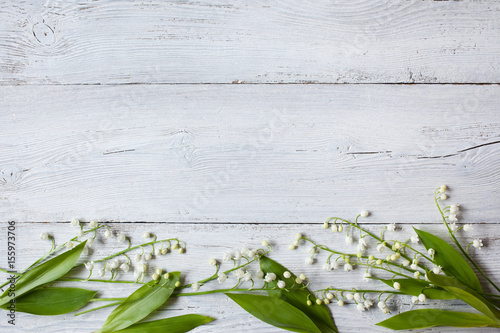 Photo Stands Lily of the valley Lily of the valley on a wooden background