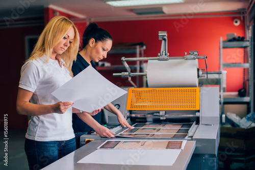 Fototapeta Two young woman working in printing factory