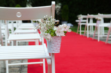 Beautiful Detail Of Wedding Decoration, Chair For Guest Decorated With Lilies, Alstroemerias And Chrysanths Flowers Behind The Red Carpet. Wedding Day Concept.