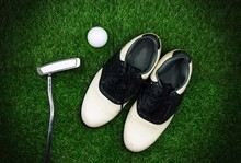 Golf Shoe And Putter And Golf Ball Are On Green Grass