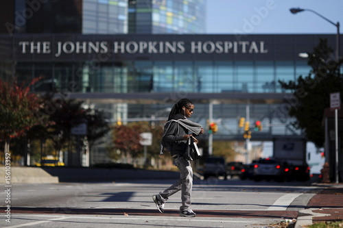 A man crosses a street in front of the John Hopkins Hospital