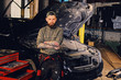 Bearded mechanics with crossed arms posing near a car.