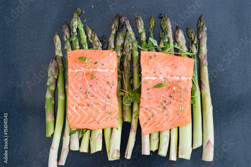 Poster Sushi bar Raw uncooked salmon and asparagus on baking tray