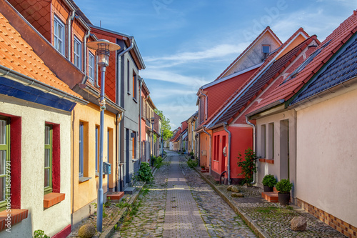 Fotografie, Obraz  View down a historic cobble stone street with old colorful fishing cottages on a sunny day