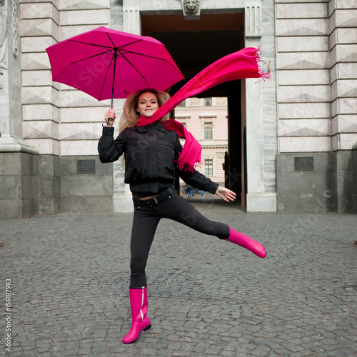 Fotografia  Beautiful young and happy blond woman with colorful umbrella on the street