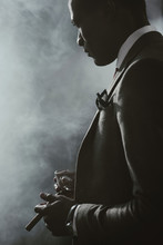 Confident African American Businessman In Suit With Glass Of Whiskey Smoking Cigar