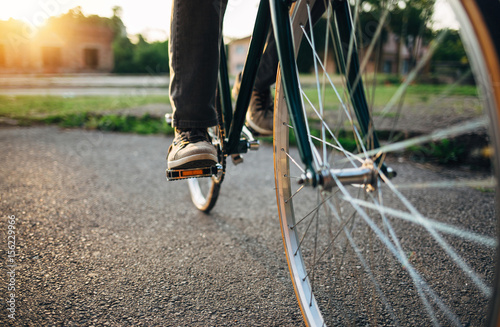 Tuinposter Fiets Riding bicycle at sunset