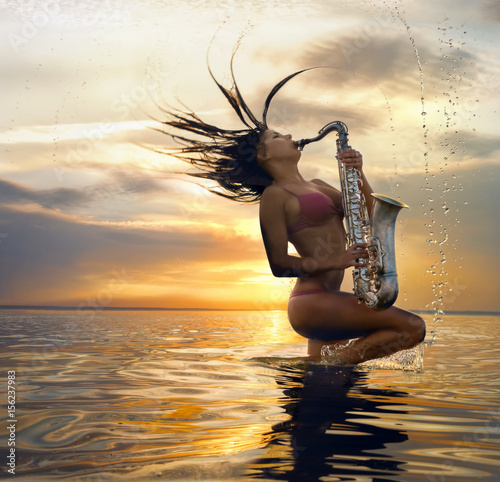Fototapeta Young sexy woman with sax with splash of water against sunset background