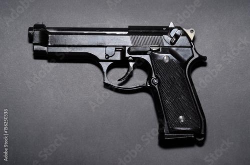 Used black metal 9mm pistol gun on black background Wallpaper Mural