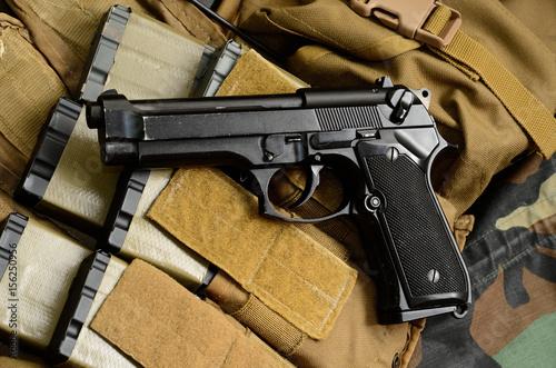 Pistol gun with military equipment. Canvas Print