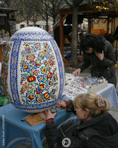 A woman paints a giant Easter egg at a traditional Easter