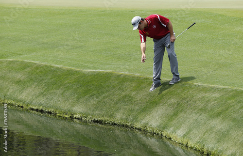 South Africa\'s Louis Oosthuizen looks for his ball in the water on ...