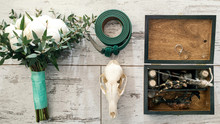 Top View Of Green Groom's Belt, Skull, Wedding Bouquet Of White Peony, Wooden Box With Wedding Rings, Bird's Paws, Feathers, Empty Bottles And Stones On Wooden Background