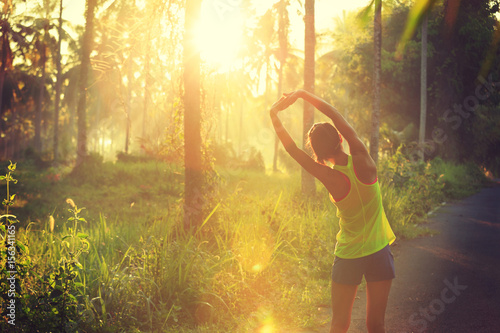 Foto  Young female runner stretching arms before running at morning forest trail
