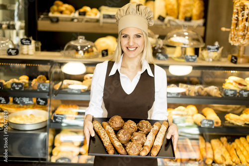 In de dag Bakkerij Beautiful female bakery posing with various types of pastries and breads in the baker shop