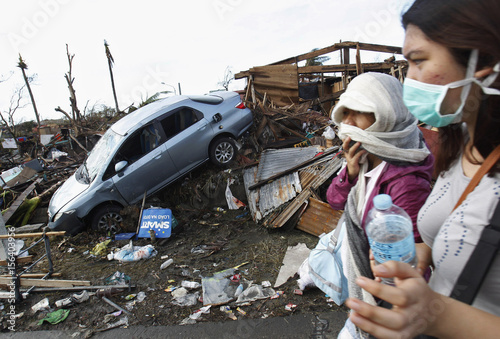 People covering their faces pass a car in debris after super