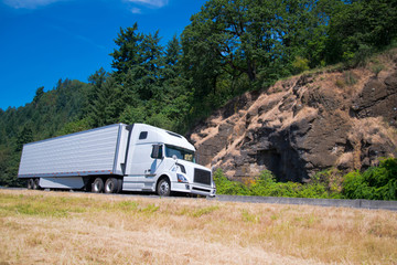 White semi truck trailer going highway with rocks green trees