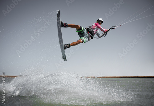 Professional kitesurfing rider sportsman jumps high acrobatics kiteboarding raley trick  with huge water splash. Recreational activity and extreme active water sports, hobby and fun in summer time