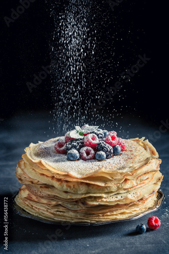Tasty stack of pancakes with berries and powder sugar