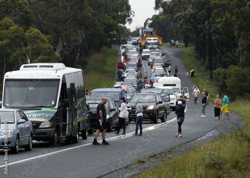 Motorists walk around their stationary cars while caught in