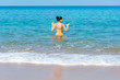 woman enjoy on the beach by sitting on the sand with light swell of the sea approach touching to the body
