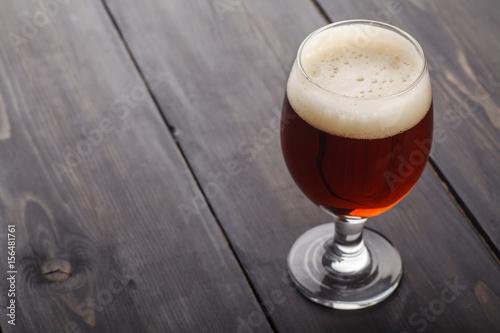 Photo  Red ale on dark wood
