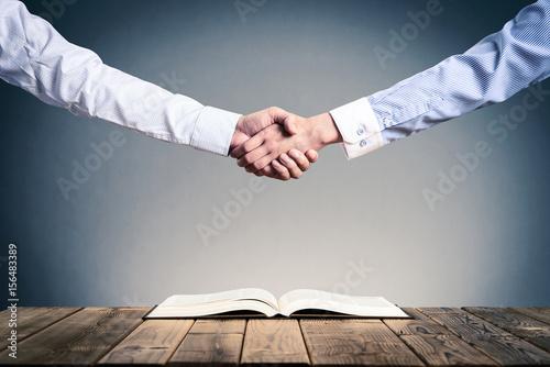 Fotografía  開いて置いてある本,ビジネスマンの握手