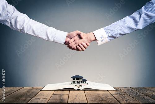Photo 本の上に置かれた住宅模型,ビジネスマンの握手