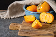 Ripe orange persimmon in a blue bowl on a wooden tray. Diet, or the concept of vegetarian food. Dark background.