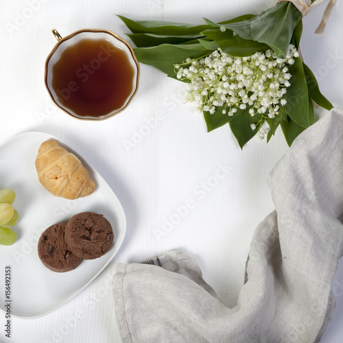 Staande foto Lelietje van dalen white cup of coffee, a bouquet of lilies of the valley, a notepad for notes and a saucer with two brownie cookies. Breakfast. Copy space