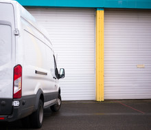 Commercial Van For Transporting Cargo Waiting By The Warehouse Gate