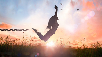 World environment day concept: Silhouette of a girl jumping and broken chains at autumn sunset meadow with her hands raised