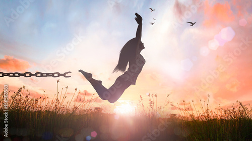 Fényképezés  World environment day concept: Silhouette of a girl jumping and broken chains at