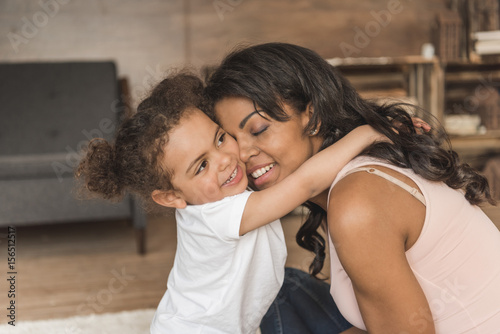 Photo  little daughter hugging smiling mother while spending time at home