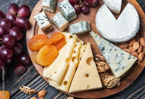 Plakat Asortowany świeży ser, owoc i dokrętki na drewnianym stole ,.