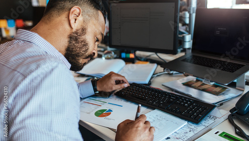 Photo  Businessman making notes at his office desk.
