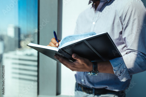 Closeup of a business investor writing in diary. Canvas Print