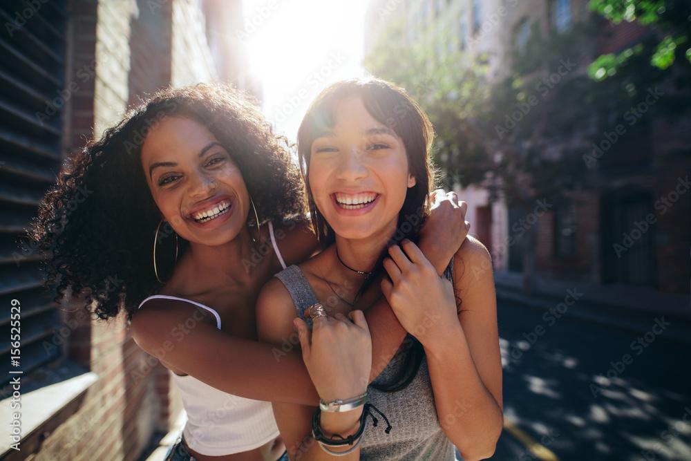 Fototapeta Two young women having fun on city street
