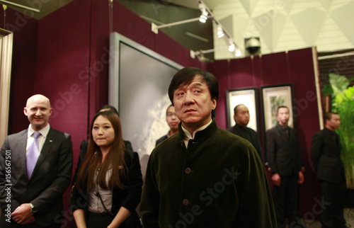 Kung Fu superstar Chan stands in front of paintings before