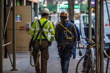 Two Construction Workers Walk Together Down A New York City Sidewalk