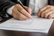 Businessman or job seeker signing on resume form.