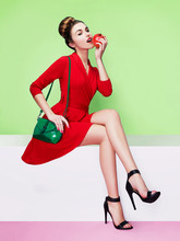Beautiful Woman Wearing Red Dress, Green Purse And Black Heels Shoes. Eating A Red Apple.