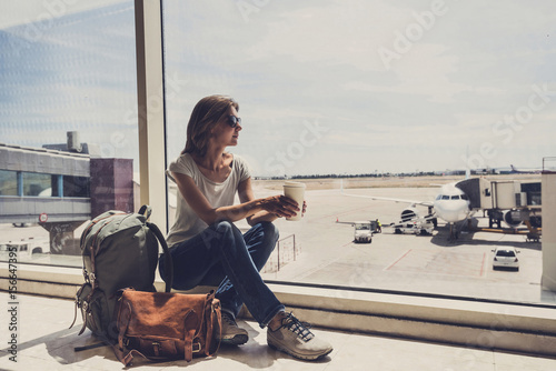 Fotografía  Young woman in the airport, looking through the window at planes and drinking co