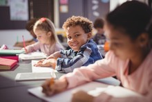 Portrait Of Smiling Schoolboy Doing His Homework In Classroom