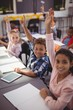 Portrait of happy schoolkids raising their hands in classroom