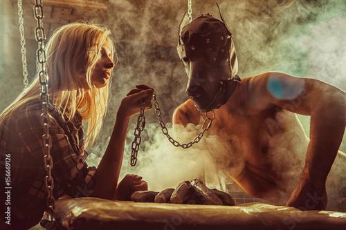 Plakat Młoda para w grze RPG, dziewczyna trzyma człowieka w masce psa na łańcuchu.