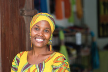 Young African Woman In Traditional Clothes Standing In Entrance Of Her Store, Smiling At Camera